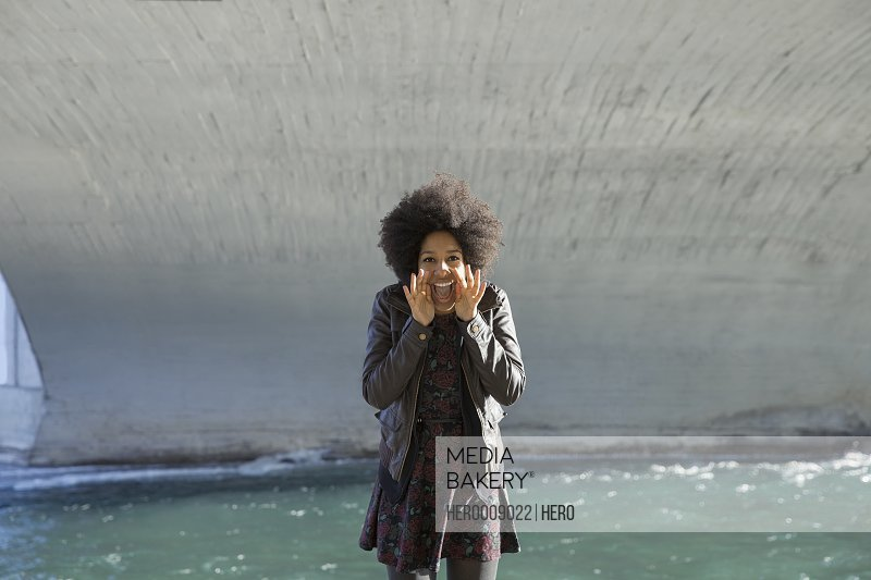 Portrait of excited woman shouting under bridge