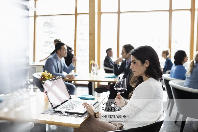 Businesswoman drinking red wine and working at laptop in restaurant