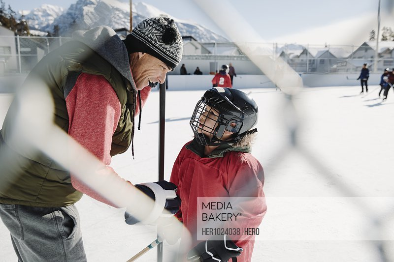 Father and son playing outdoor ice hockey
