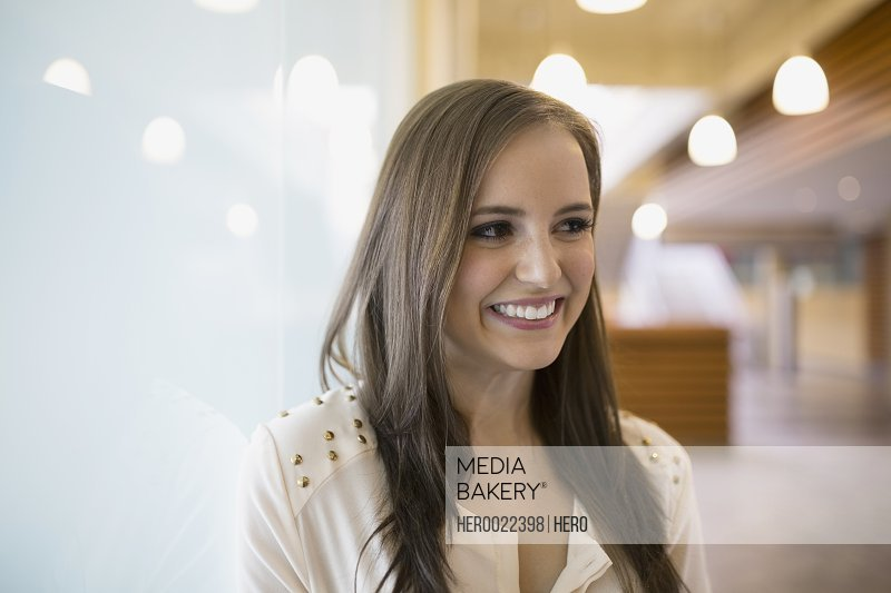 Portrait smiling brunette businesswoman looking away frosted glass