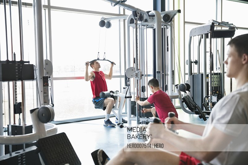 Men using weight machines in fitness center