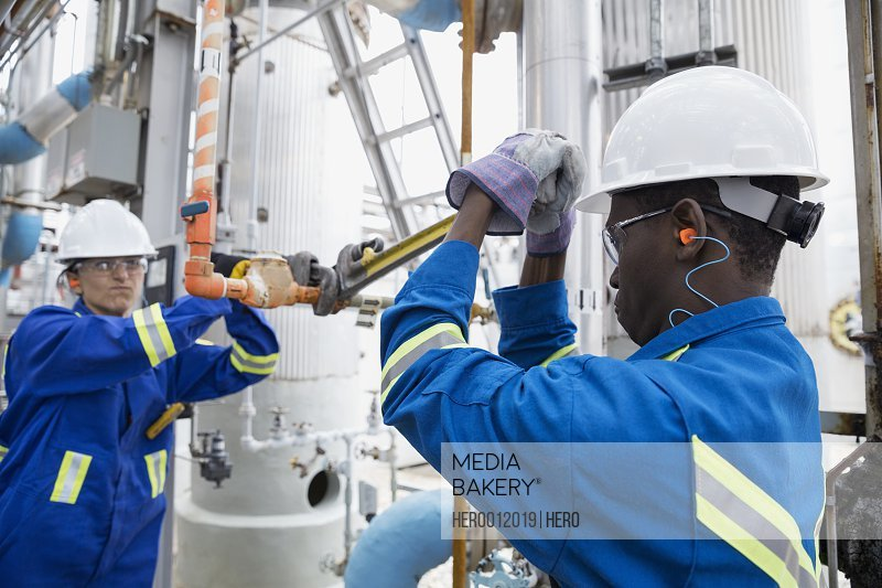 Workers repairing pipe at gas plant