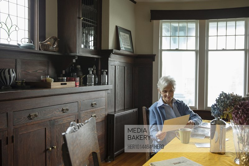 Senior woman looking through photographs at home
