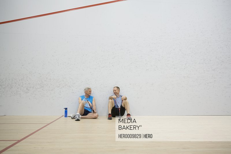 Men resting on squash court