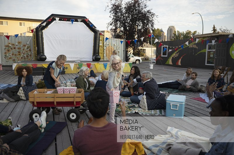 Girl selling popcorn to crowd waiting for movie in park to start