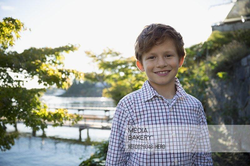 Portrait smiling boy lakeside
