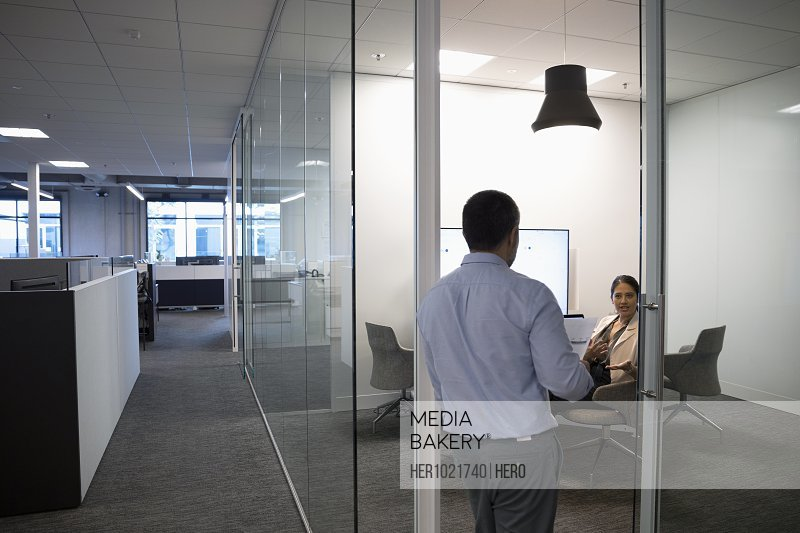 Businessman and businesswoman talking in conference room doorway