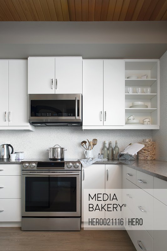 Modern white kitchen with stainless steel appliances