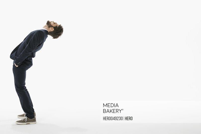 Businessman leaning backward against white background