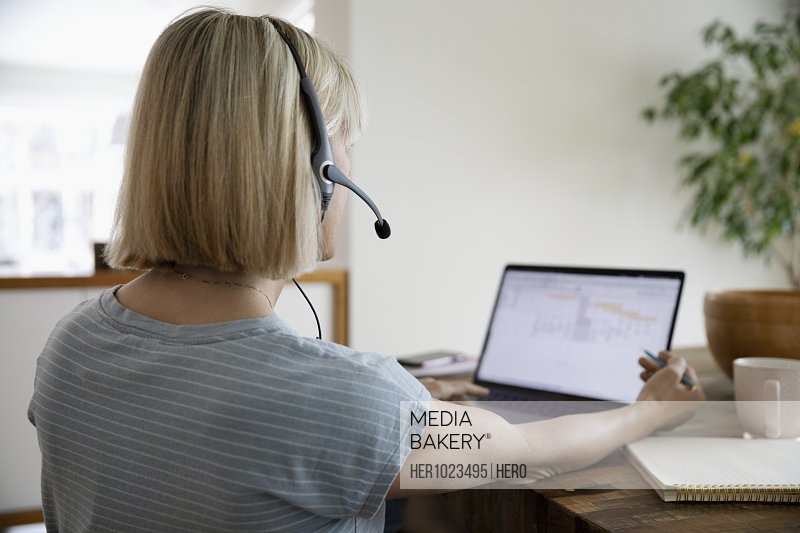 Woman in headset working from home, using laptop at table