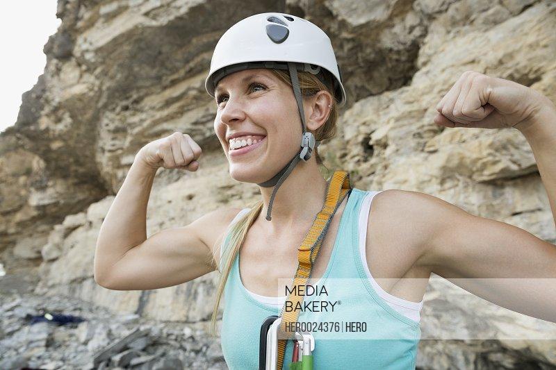 Portrait confident female rock climber flexing biceps