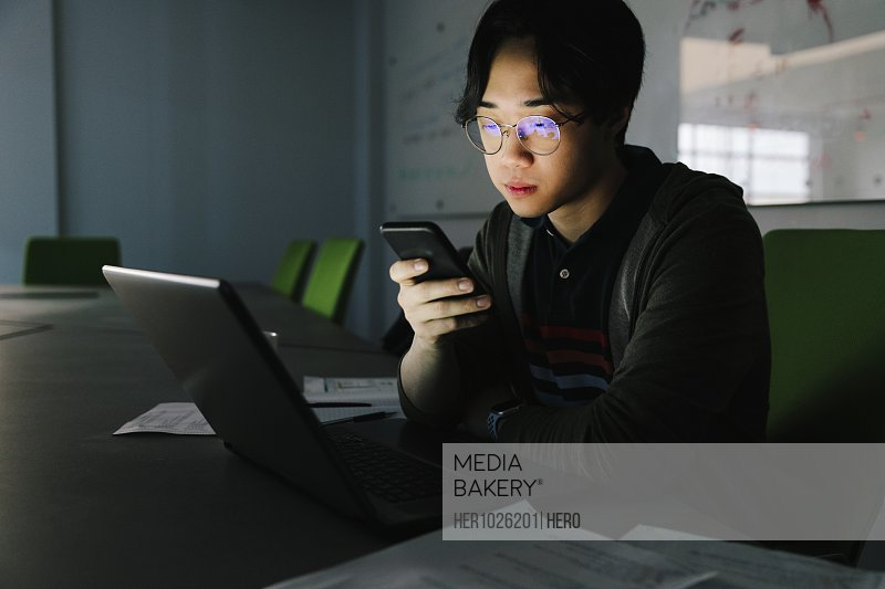Focused male computer programmer working late, using smart phone in office