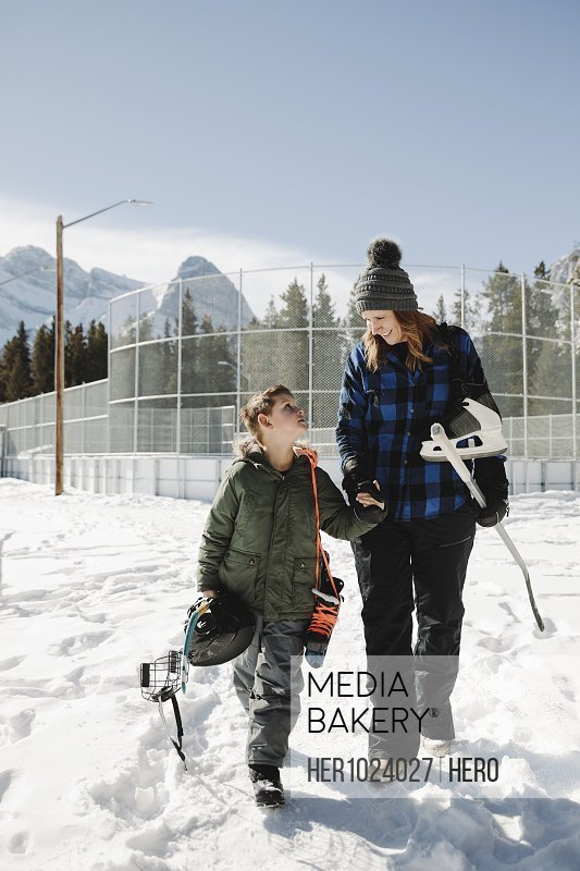 Affectionate mother and son walking with outdoor ice hockey equipment