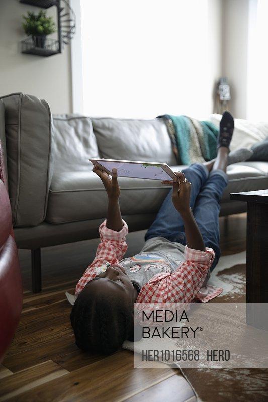 Tween girl using digital tablet on living room floor