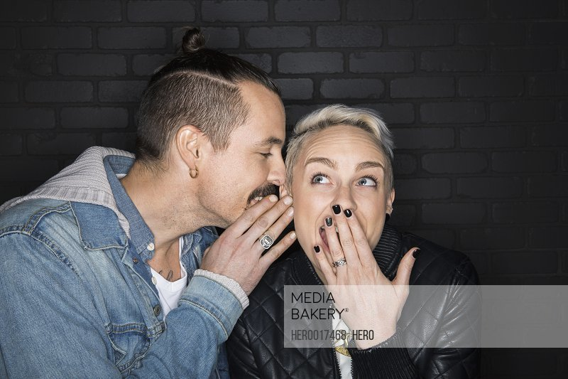 Man whispering into surprised womans ear