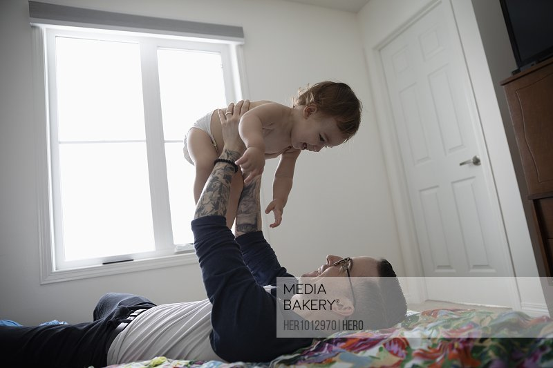 Father lifting baby son overhead on bed