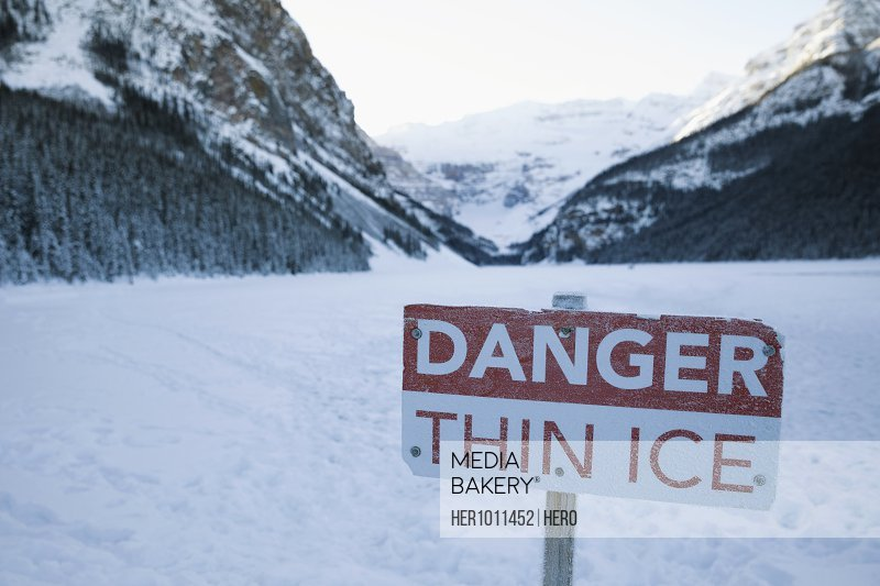 Danger Thin Ice sign on snowy mountain lake