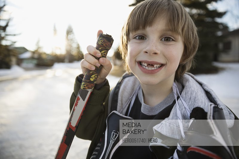 Portrait enthusiastic gap toothed boy holding ice hockey stick and ice skates on snowy road