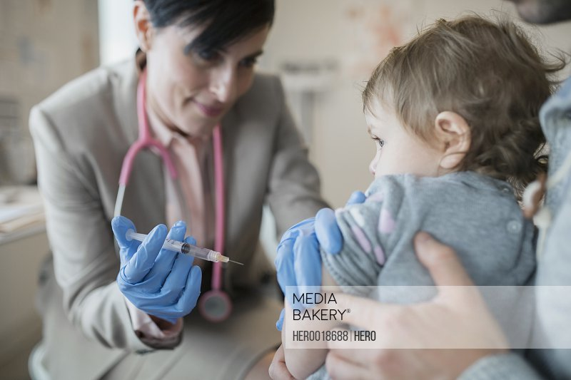 Pediatrician giving baby girl vaccination in clinic