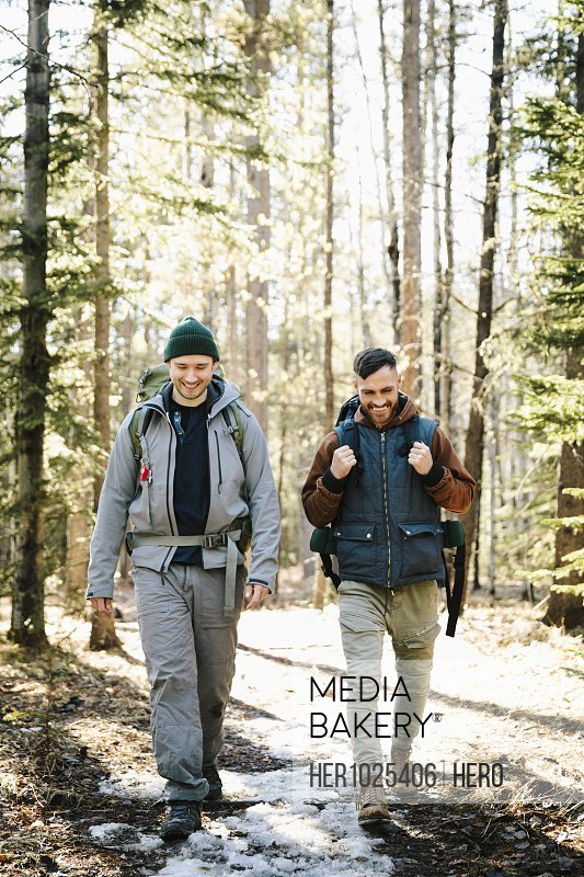 Male friends with backpacks hiking in snowy woods