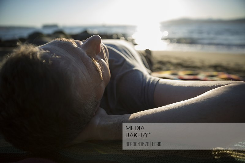 Close up serene man laying on sunny beach