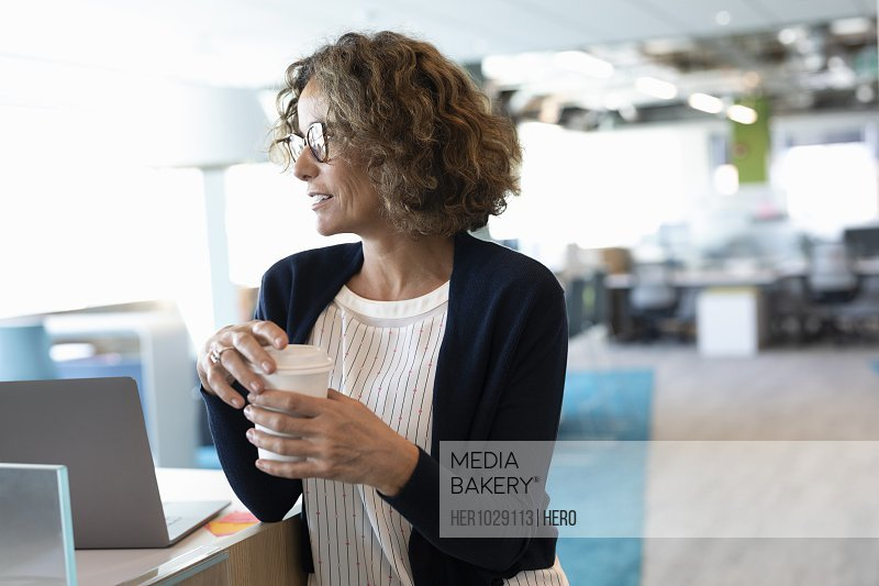 Mature businesswoman in modern office with coffee cup
