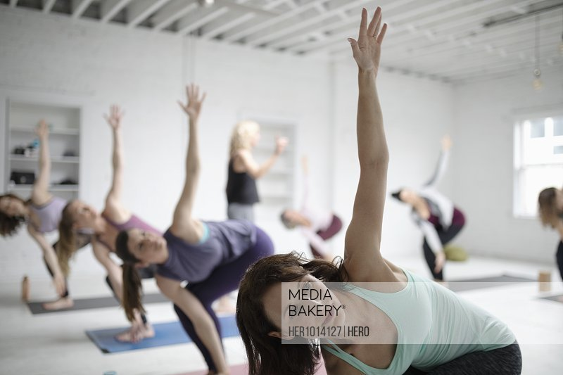 Women practicing twisted chair pose in yoga class