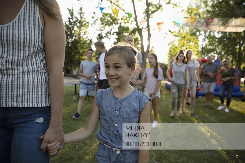 Smiling girl holding hands with mother at summer neighborhood block party in park