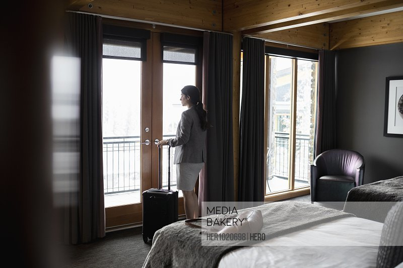 Thoughtful businesswoman looking out hotel room window