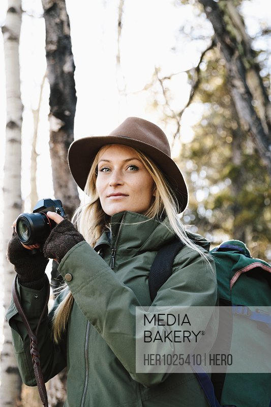 Portrait confident woman with backpack and camera hiking
