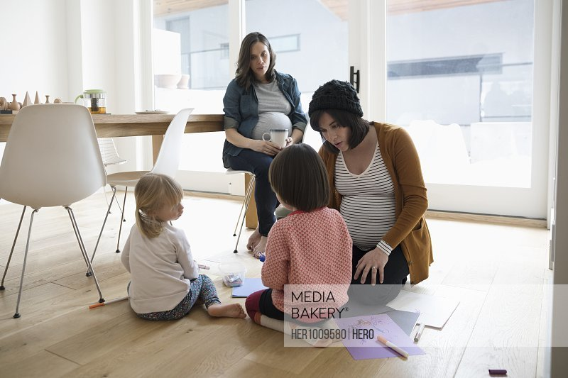 Pregnant mothers and toddler daughters playing on floor, enjoying play date