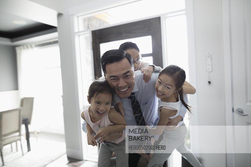 Portrait playful children hanging on businessman father