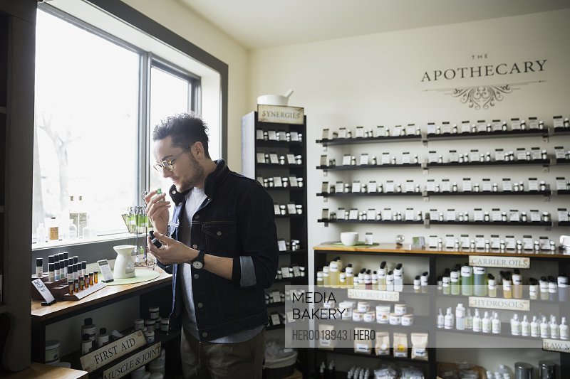 Man smelling essential oils in apothecary shop