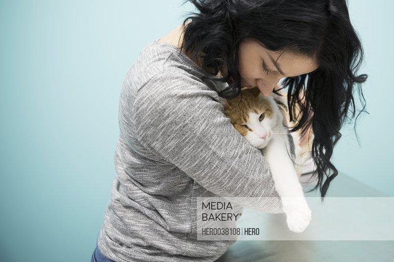 Pet owner hugging cat