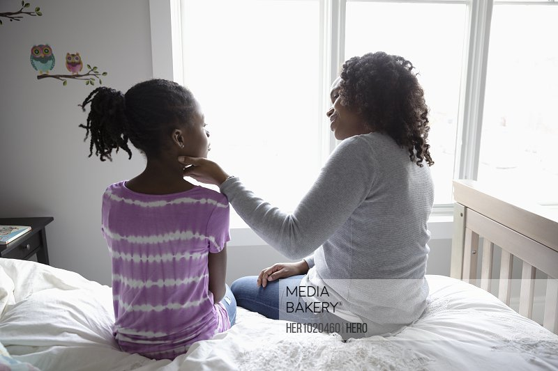 Affectionate mother and tween daughter bonding, talking on bed