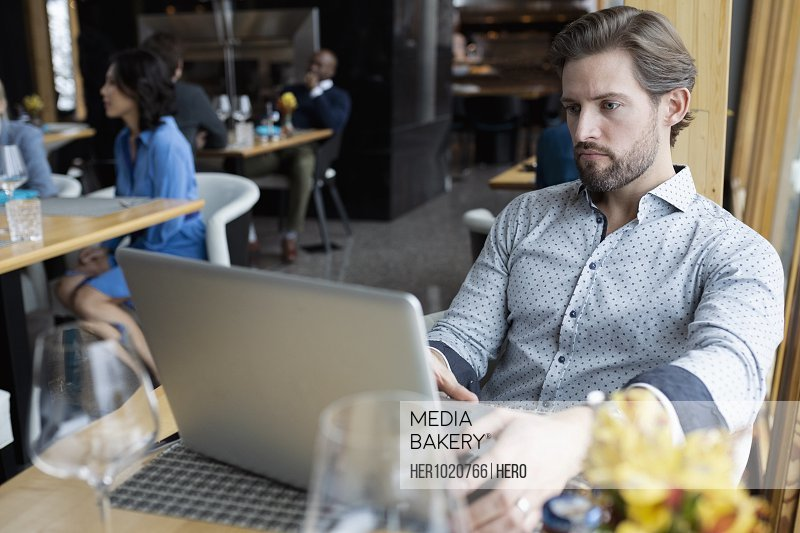 Focused businessman working at laptop at restaurant table