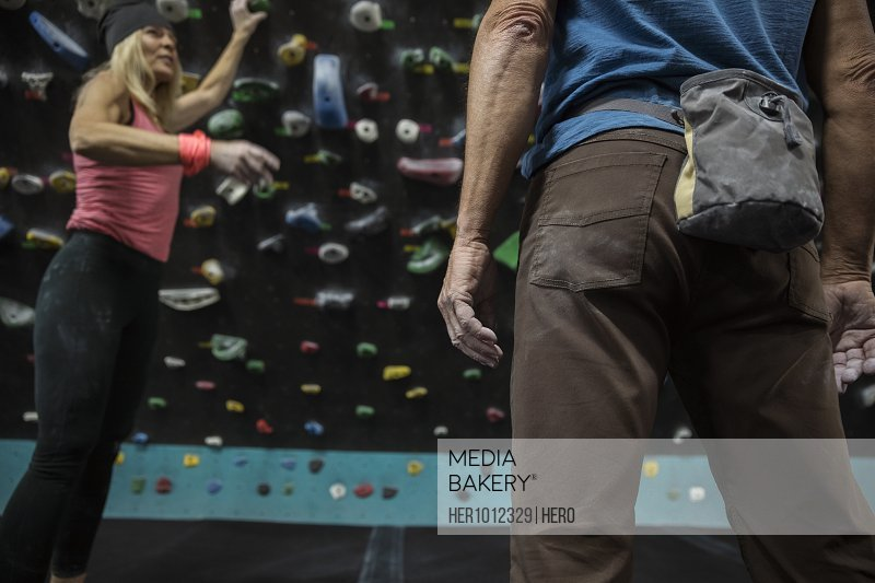 Female rock climber gesturing, talking with male rock climber at climbing wall in climbing gym