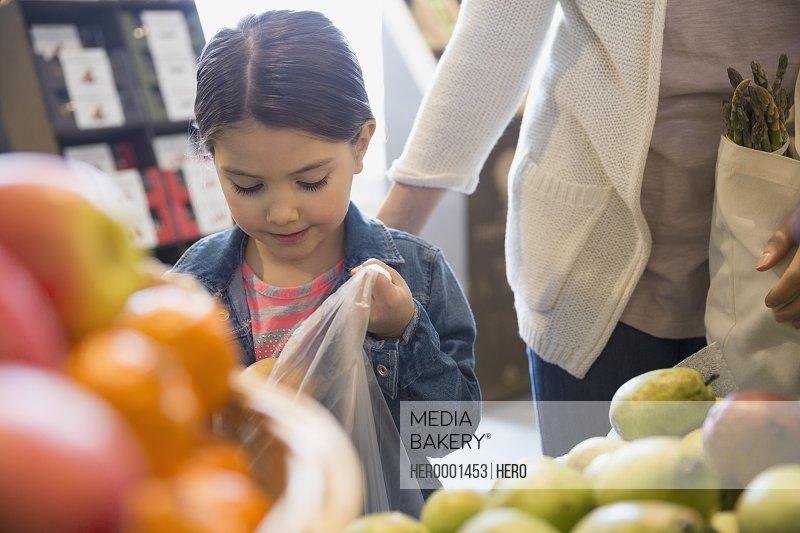 Girl bagging produce in market