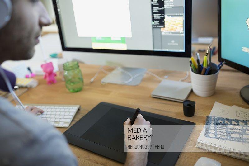 Designer using graphics tablet at computer