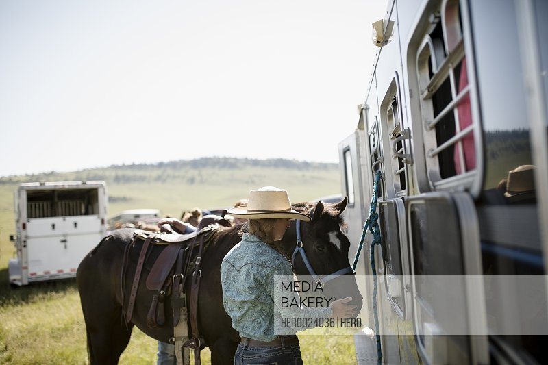Female rancher with horse at horse trailer