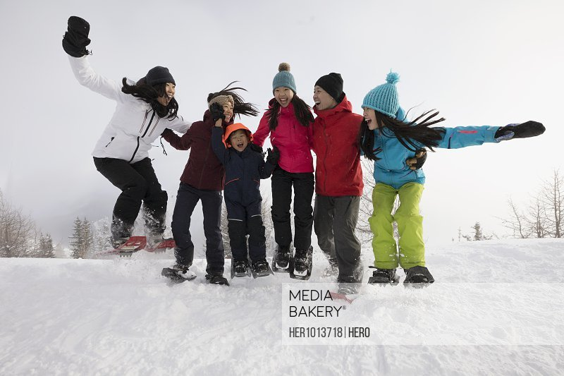 Playful, energetic family snowshoers jumping in snow