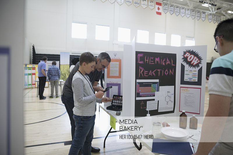 Father and middle school student son viewing science project at science fair
