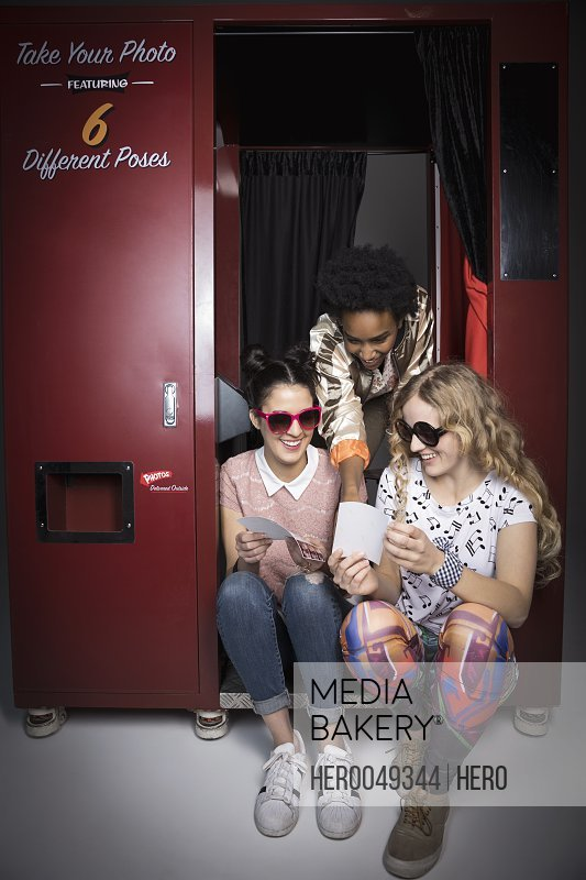 Women friends in sunglasses viewing photographs at photo booth