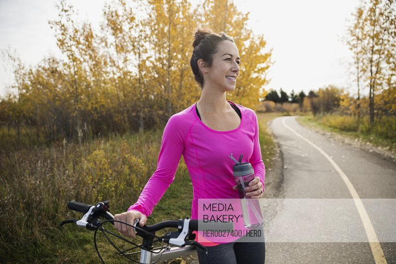 Woman with bicycle water bottle resting autumn path