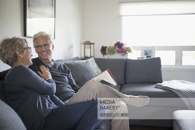 Smiling senior couple relaxing, reading book on living room sofa