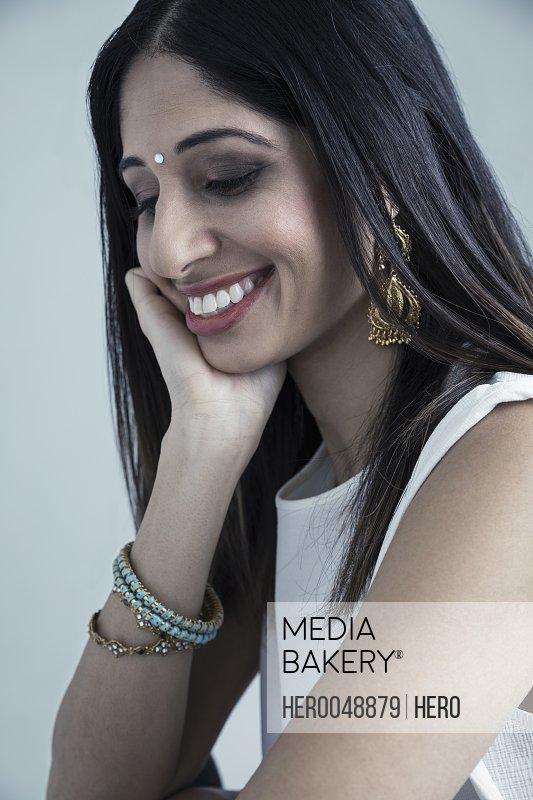 Portrait smiling brunette Indian woman wearing bindi looking down
