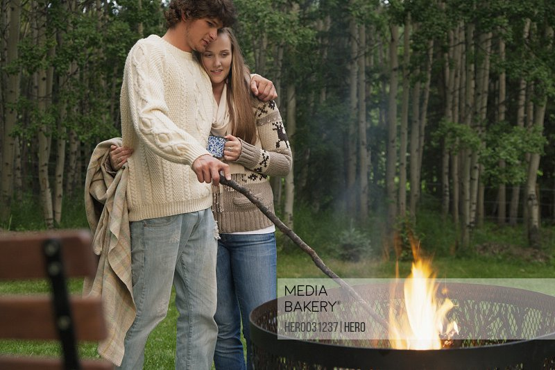 young adult couple cuddling by fire outdoors