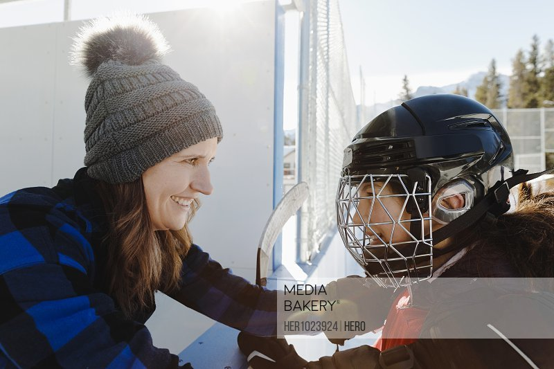 Mother and daughter playing outdoor ice hockey