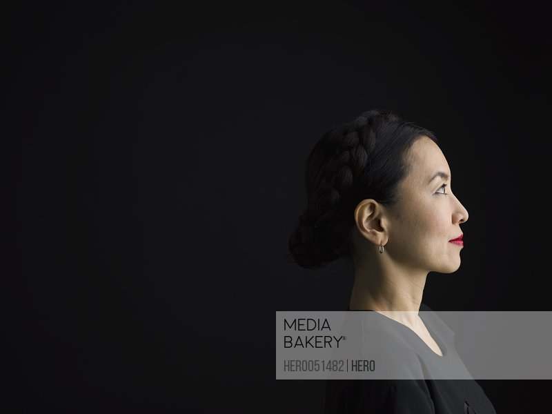 Profile portrait pensive Asian woman looking away against black background