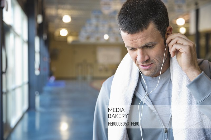 Man listening to music on earbuds at fitness center